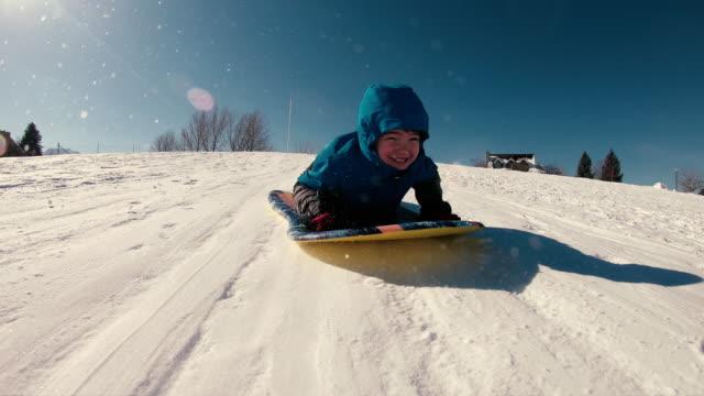 ung pojke älskar snö sledding - vintersport bildbanksvideor och videomaterial från bakom kulisserna