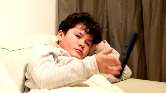 Young boy lying on sofa and watching tv at home 12 years old child boy watching tv sitting on a couch at home alone changing channels stock videos & royalty-free footage