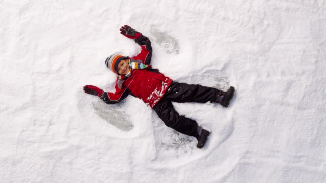 Young boy making snow angel in winter video