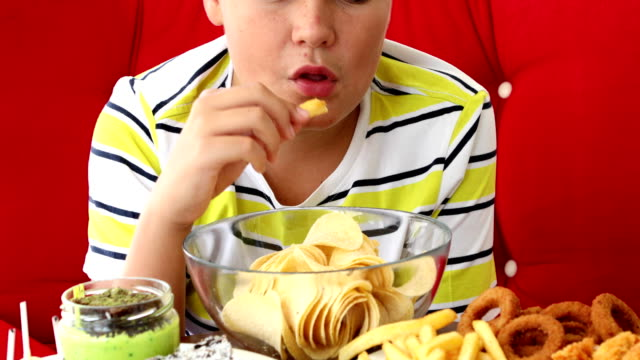 Young boy mouth sealed with duct tape with fast food plate Unhappy young boy with taped mouth and fast food plates. Healthy diet people food concept onion ring stock videos & royalty-free footage