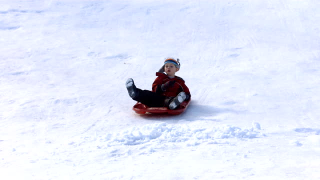 Young boy on fast sled hits pile of snow video
