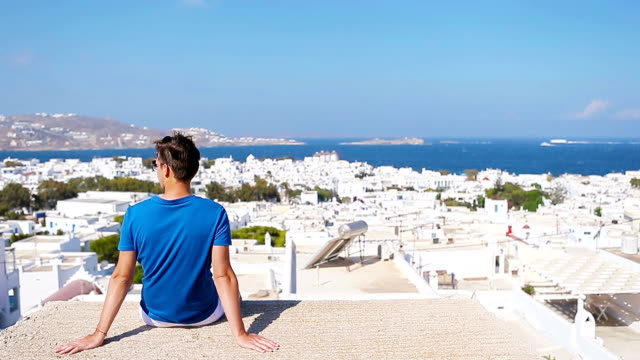 Young boy on street with amazing view on Mykonos, Greece. Beautiful famous background video