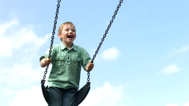 Young boy on swing, slow motion video