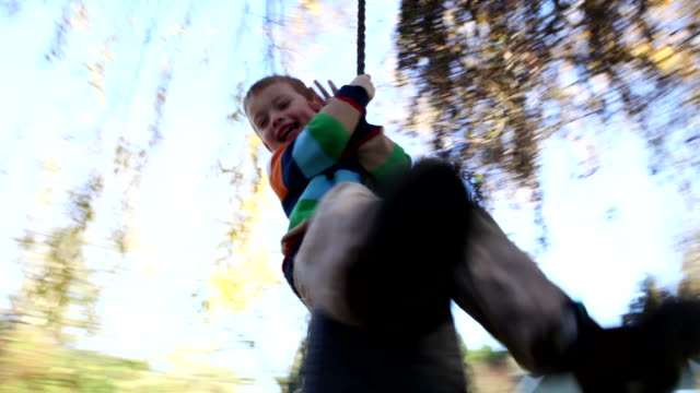 Young boy on tire swing, fast dolly movement video