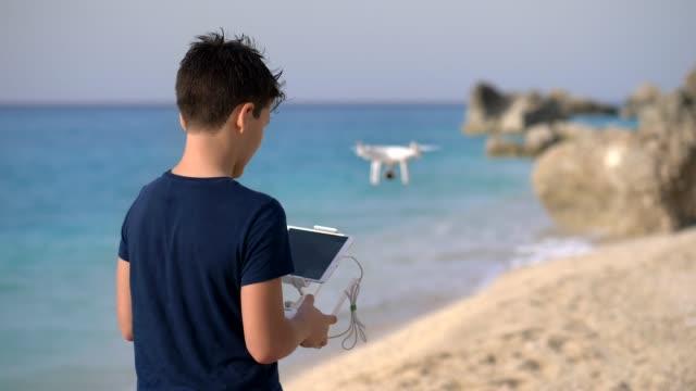 바다의 해 안에 비행 무인 항공기를 운영 하는 젊은 소년. uhd - 무인항공기 스톡 비디오 및 b-롤 화면