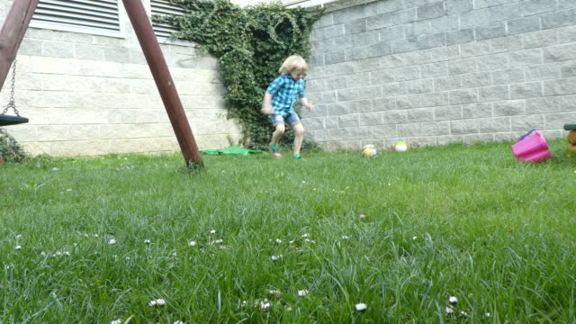 Young boy playing a ball in backyard. Young boy kicking/playing a ball in backyard. only boys stock videos & royalty-free footage