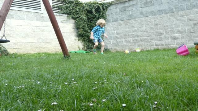 young boy playing a ball in backyard. - solo bambini maschi video stock e b–roll