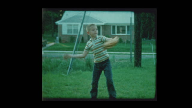 young boy playing catch with baseball in suburban backyard 1960 - baseball stock videos and b-roll footage