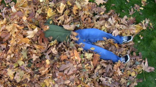 vidéos et rushes de jeune garçon jouant avec un tas de feuilles mortes - entassé