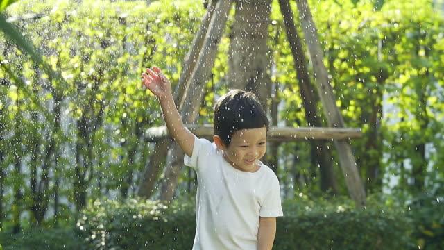 暑い夏の日に彼の裏庭の水スプリンクラーを自宅で遊ぶ少年。(スローモーション vdo カメラで撮影) - ガーデニング点の映像素材/bロール