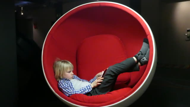 Young boy playing on a digital tablet. Young boy sitting on the red armchair playing on a digital tablet. one boy only stock videos & royalty-free footage