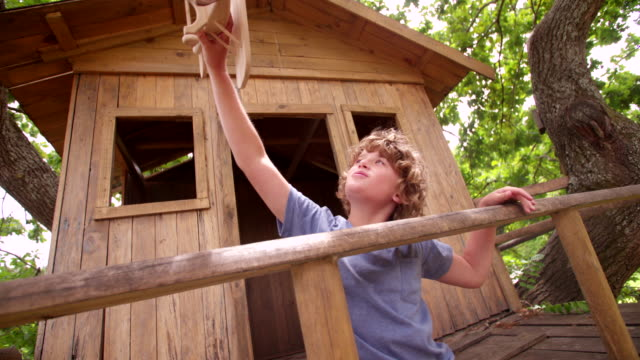 Young boy playing with a wooden toy plane in treehouse video