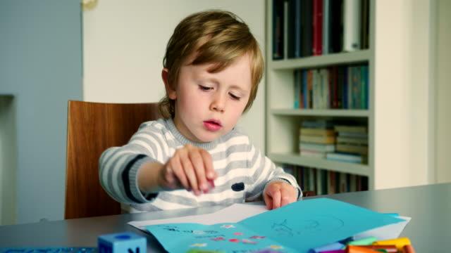 kleiner junge spielt mit aufkleber - aufkleber stock-videos und b-roll-filmmaterial
