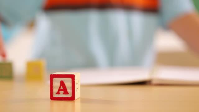 młody chłopiec bawi się z alfabet bloki - klocek filmów i materiałów b-roll