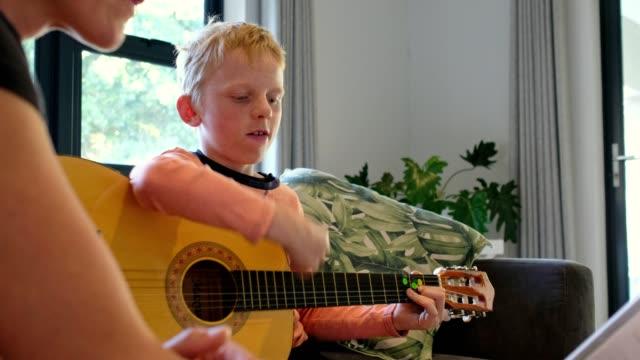ung pojke praxis sin gitarr via telefonkonferens med sin musiklärare - akustisk gitarr bildbanksvideor och videomaterial från bakom kulisserna