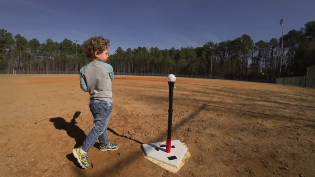 Young boy practicing batting on an empty baseball field video