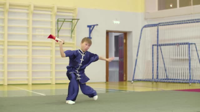 Young boy practicing exercises changquan with sword at martial arts training