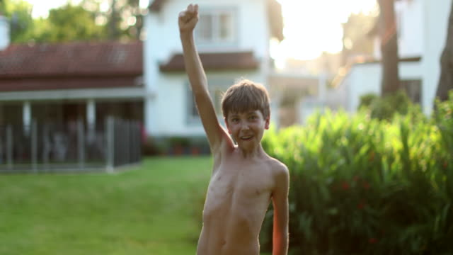 Young boy raising arm in the air in celebration outdoors