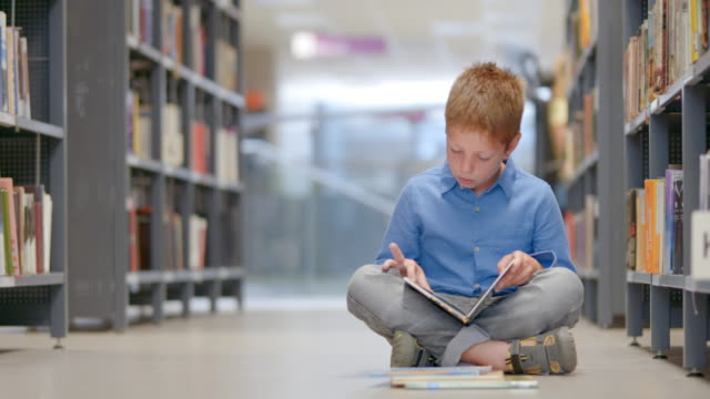 DS Young boy reading a book sitting in library aisle Medium low angle dolly shot of a young boy sitting by the bookshelf in the library aisle and reading a book. cross legged stock videos & royalty-free footage