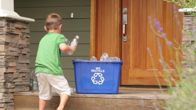 młody chłopiec recyklingu - odzyskiwanie i przetwarzanie surowców wtórnych filmów i materiałów b-roll
