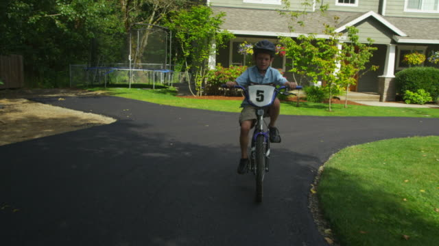 Young boy riding bicycle in driveway, tracking shot video