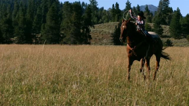 молодой мальчик езда лошадь с лассо, замедленная съемка - запад стоковые видео и кадры b-roll