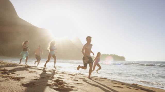 Young boy running along beach as family follows video