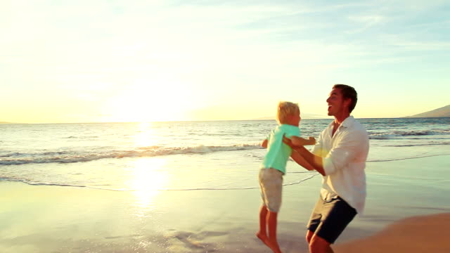 Young Boy Running for Fun into his Fathers Arms at the Beach at Sunset. video