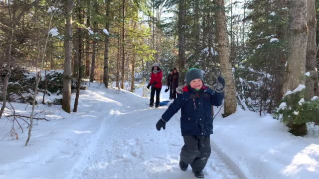 ung pojke som springer i skogen på vintern efter snöstorm - snow kids bildbanksvideor och videomaterial från bakom kulisserna