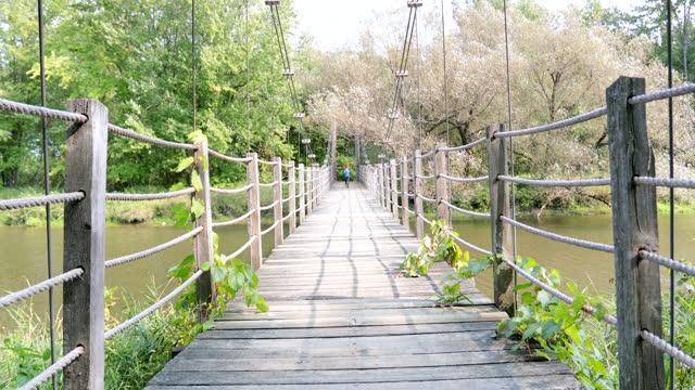 Young Boy Running on Suspension Bridge in Summer