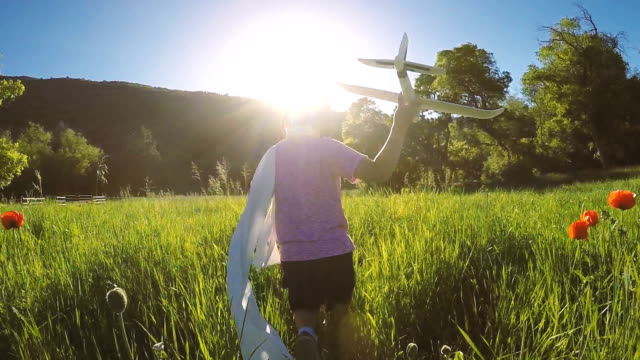 Young Boy Runs through Field Flying Airplane video