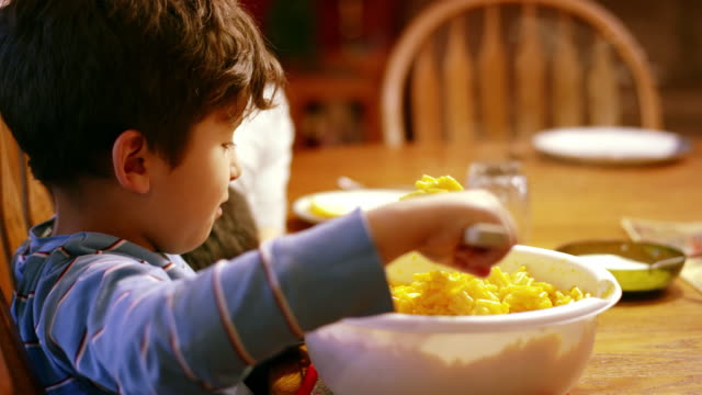 Young boy scooping macaroni and cheese onto plate at dinner table Young boy scooping macaroni and cheese onto plate at dinner table macaroni stock videos & royalty-free footage
