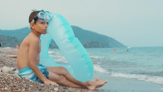 ung pojke sitter på stranden. liten pojke förbereder uppblåsbara cirkel dopp - inflatable ring bildbanksvideor och videomaterial från bakom kulisserna