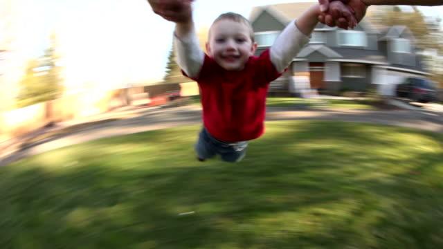 stockvideo's en b-roll-footage met young boy spinning around in parent's hands - garden house