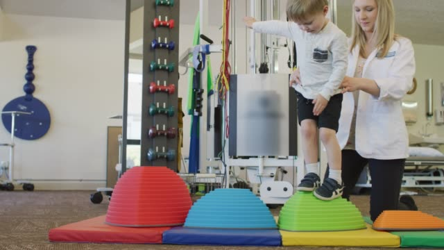young boy steps from object to object - fisioterapia video stock e b–roll