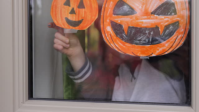 Young Boy sticking his pumpkin drawing on home window Young Boy sticking his pumpkin drawing on home window during the Coronavirus Covid-19 crisis. halloween covid stock videos & royalty-free footage