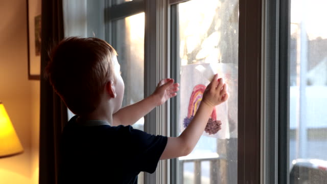 Video Young Boy sticking his rainbow drawing on home window during the Covid-19 crisis at sunset