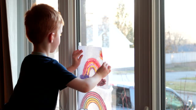 Young Boy sticking his rainbow drawing on home window during the Covid-19 crisis at sunset Young Boy sticking his rainbow drawing on home window during the Coronavirus Covid-19 crisis at sunset at say hello to neighbours.  Many people are putting a rainbow to tell neighbours that people inside this house are ok. #Stayathome stay home stock videos & royalty-free footage