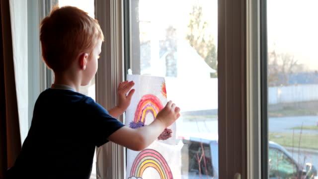 vídeos y material grabado en eventos de stock de young boy metiendo su arco iris dibujando en la ventana de casa durante la crisis de covid-19 al atardecer - stay home