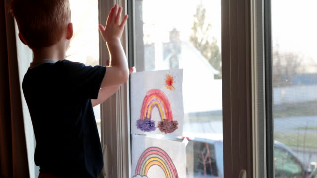 young boy sticking his rainbow drawing on home window during the covid-19 crisis at sunset - vicino video stock e b–roll