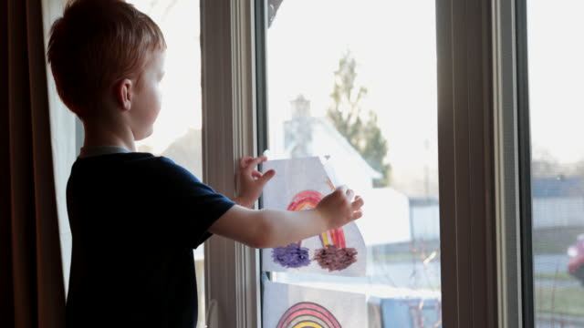Young Boy sticking his rainbow drawing on home window during the Covid-19 crisis at sunset Young Boy sticking his rainbow drawing on home window during the Coronavirus Covid-19 crisis at sunset at say hello to neighbours.  Many people are putting a rainbow to tell neighbours that people inside this house are ok. #Stayathome rainbow stock videos & royalty-free footage