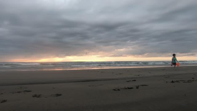 young boy superhero playing on murawai beach new zealand at sunset - solo bambini maschi video stock e b–roll