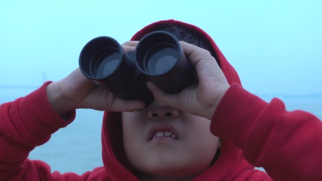Young boy surprised in looking with binoculars on tourboat Young boy looking hong kong-zhuhai-macau bridge with binoculars on tourboat independence stock videos & royalty-free footage