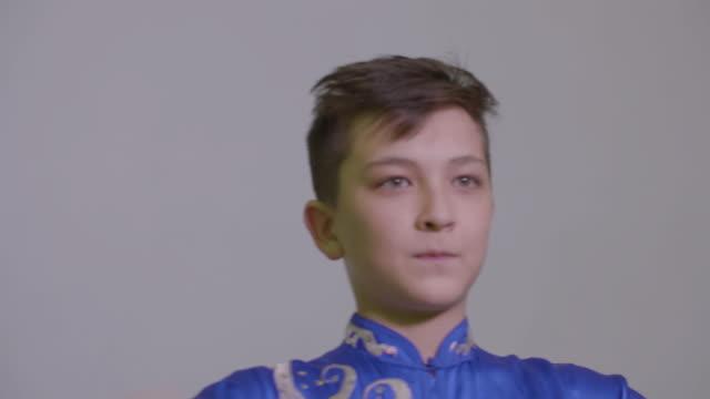 vídeos de stock, filmes e b-roll de adolescente jovem rapaz mostrando a tradicional saudação em kung fu pelo punho segurando - artes marciais