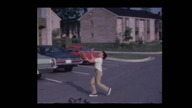 1971 Young boy tossing baseball in the air in parking lot, fakes throw to camera
