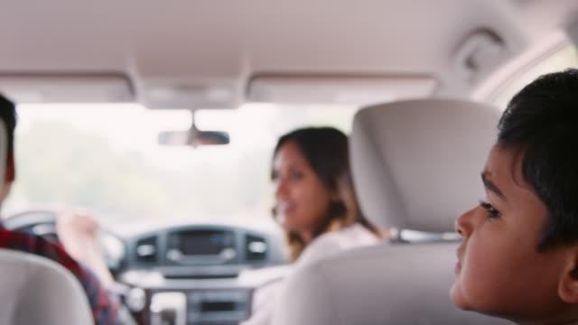vidéos et rushes de jeune garçon voyageant à l'arrière d'une voiture avec ses parents - voiture blanche