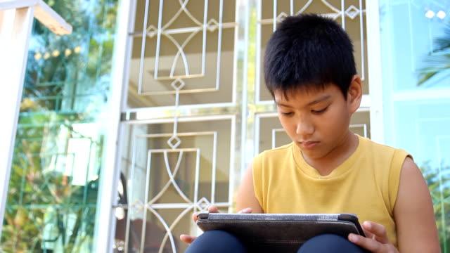 young boy using a digital tablet - dijital yerli stok videoları ve detay görüntü çekimi