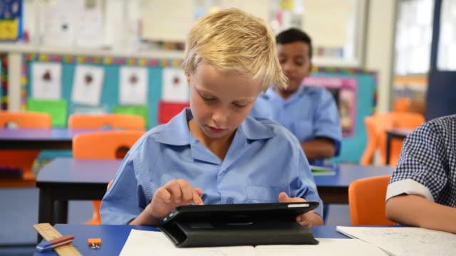 stockvideo's en b-roll-footage met jongen met behulp van digitale tablet in school klas - schooljongen