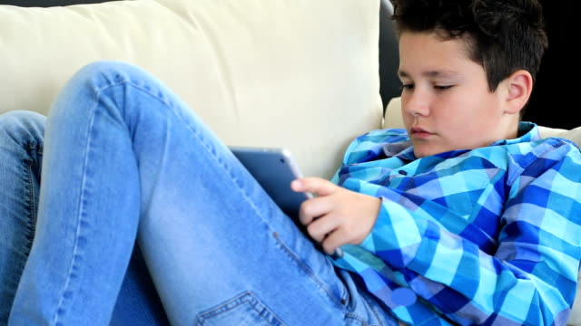 Young boy using digital tablet Portrait of a relaxed preteen boy laying sofa with digital tablet texting message or playing game at home. Technology, internet communication and people concept one boy only stock videos & royalty-free footage