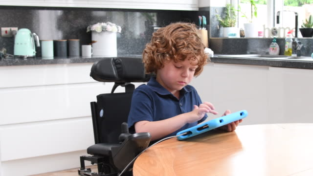 Young boy using tablet in wheelchair at home Boy with muscular dystrophy sitting at kitchen table, talking and smiling towards camera, playing game on device, cheerful expression disability stock videos & royalty-free footage